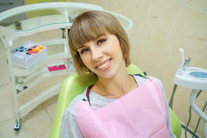 Happy woman sitting in dentist`s office, healthy teeth.  royalty free stock images