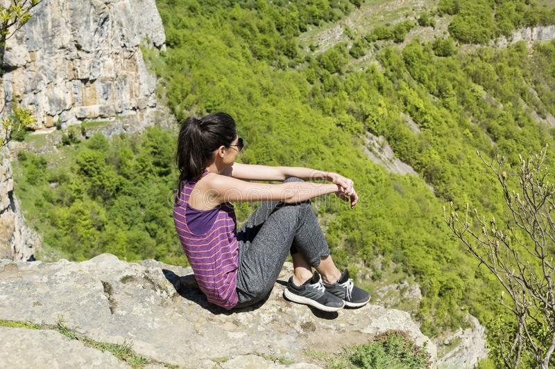 Happy Woman Sitting on the Edge of Rock in the Summer Mountain. Happy woman relaxing in a high mountain royalty free stock photos