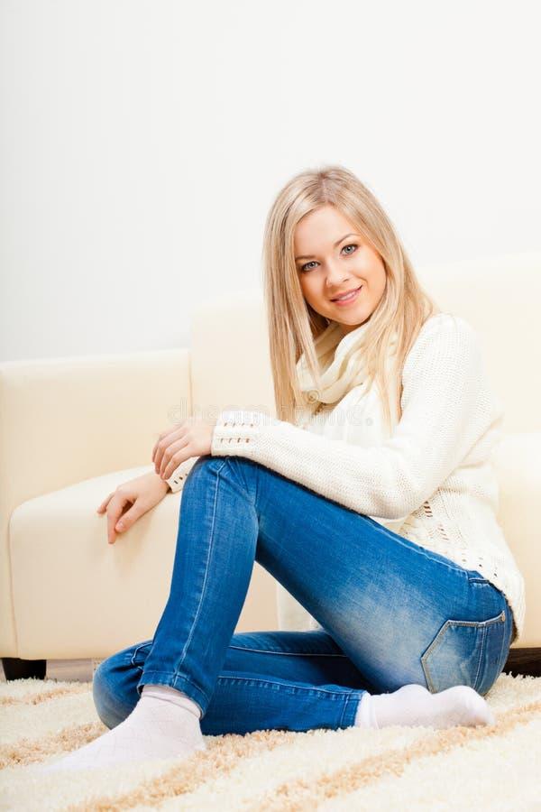 Happy woman sitting on floor stock image