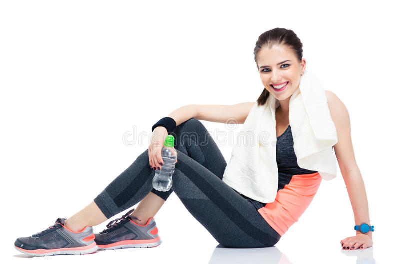 Happy woman sitting on the floor with bottle of water royalty free stock photography