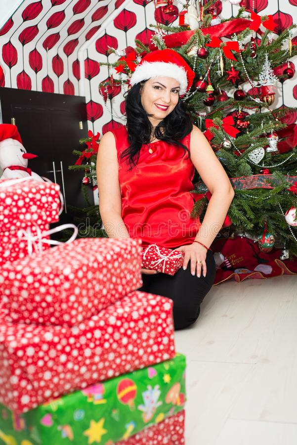 Happy woman with Christmas gifts. Happy woman sitting in front of Christmas tree with presents in her house royalty free stock photo