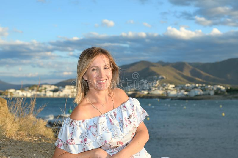 Happy woman sitting in front of a coastal landscape of the northern mediterranean on a summer afternoon with wind looking at the. Happy woman sitting in front of stock photo