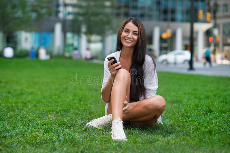 Happy woman sitting on green grass at city park and using smartphone stock images