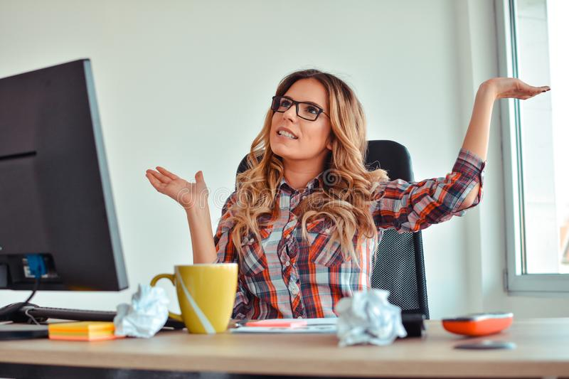 Happy woman sitting at her desk with arms up stock photo