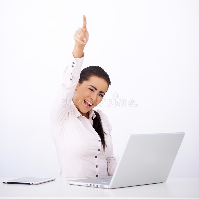 Happy woman sitting at her desk, with one arm rised royalty free stock photo