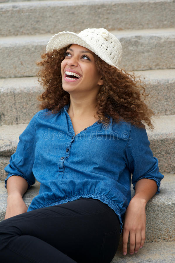 Happy woman sitting outdoors and laughing