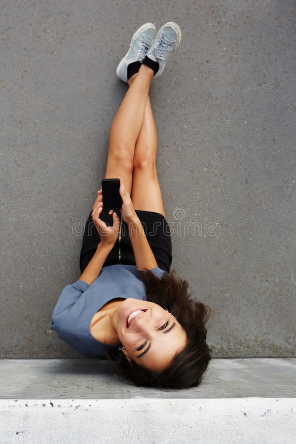 Happy woman sitting outside with smartphone and smiling. Top view portrait of happy woman sitting outside with smartphone and smiling royalty free stock photos