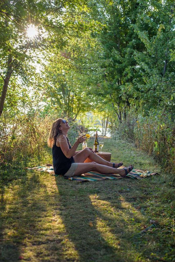 Happy woman sitting on picnic blanket with glass of wine stock photo