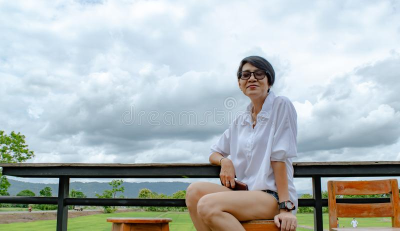 Adult woman and beautiful green field in countryside cafe. Happy woman sitting and smile at the local cafe, slow-life concept in countryside of Thailand royalty free stock image