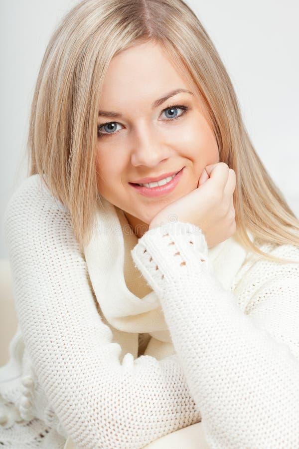Happy woman sitting on sofa royalty free stock image