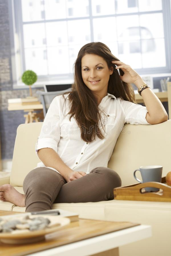 Happy woman sitting on sofa at home stock images
