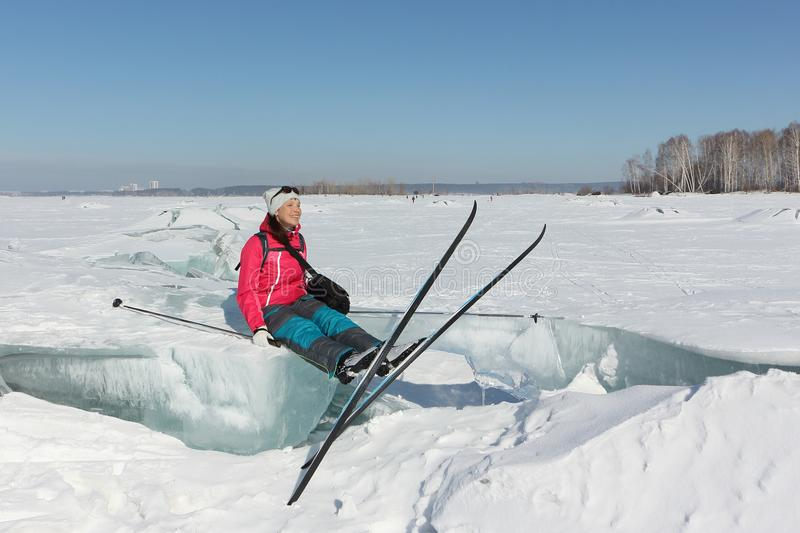 Happy woman skier sitting on an ice floe on a fro royalty free stock images