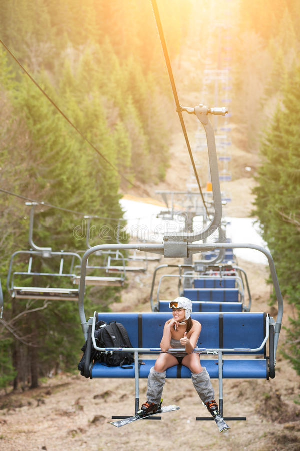Happy woman skier is sitting at ski lift and riding up to the top of mountain, showing thumbs royalty free stock photo