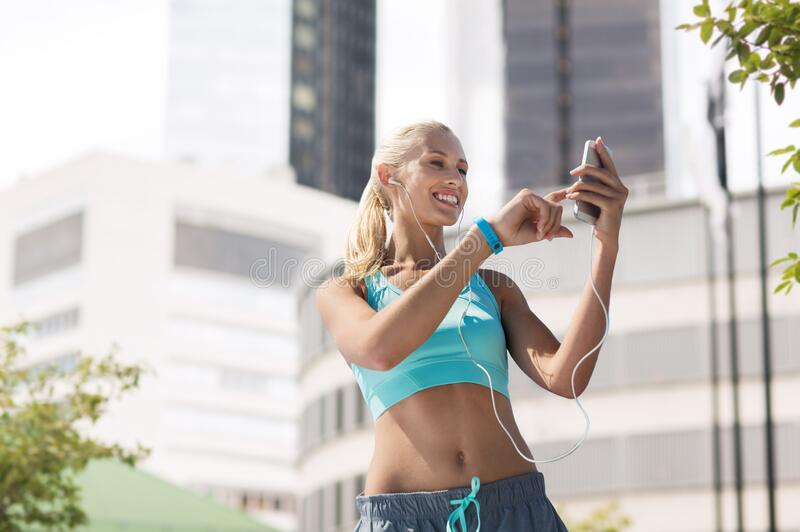 Happy woman with smartphone and earphones at city stock photos