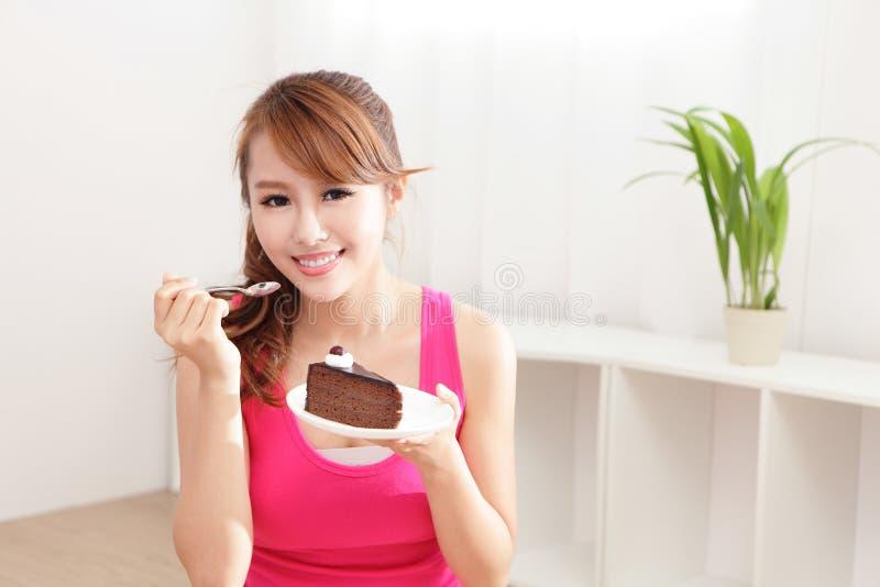 Happy woman smiles eating chocolate cake