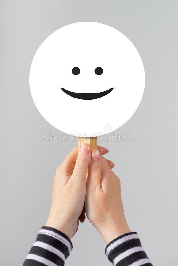 Happy woman with smiley emoticon. Casual cheerful female posing for happiness and joy concept stock image