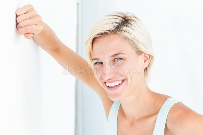 Happy woman smiling at camera with hand on wall royalty free stock photos