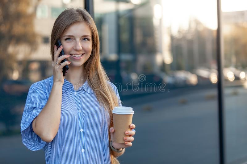 Happy woman smiling at camera, talking on mobile phone, holding a coffee to-go royalty free stock photography