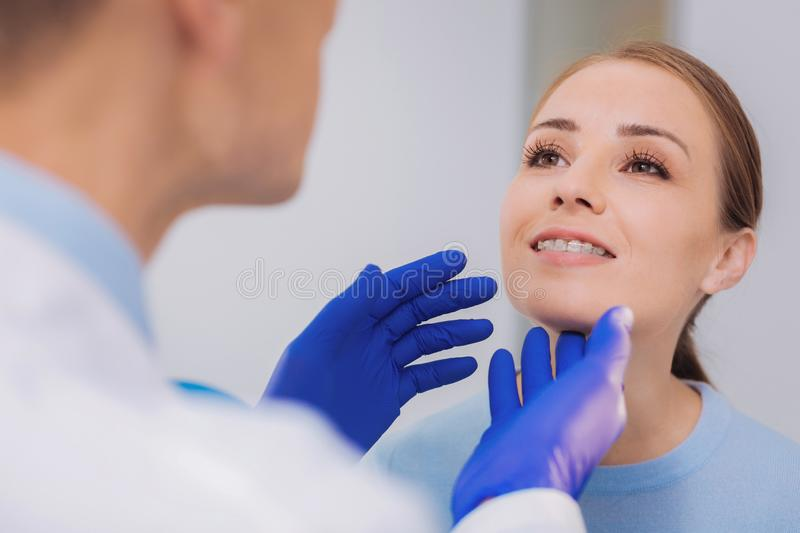 Happy woman smiling while the dentist looking at her braces. Nice braces. Cheerful responsible patient feeling confident while a qualified dentist checking her stock images