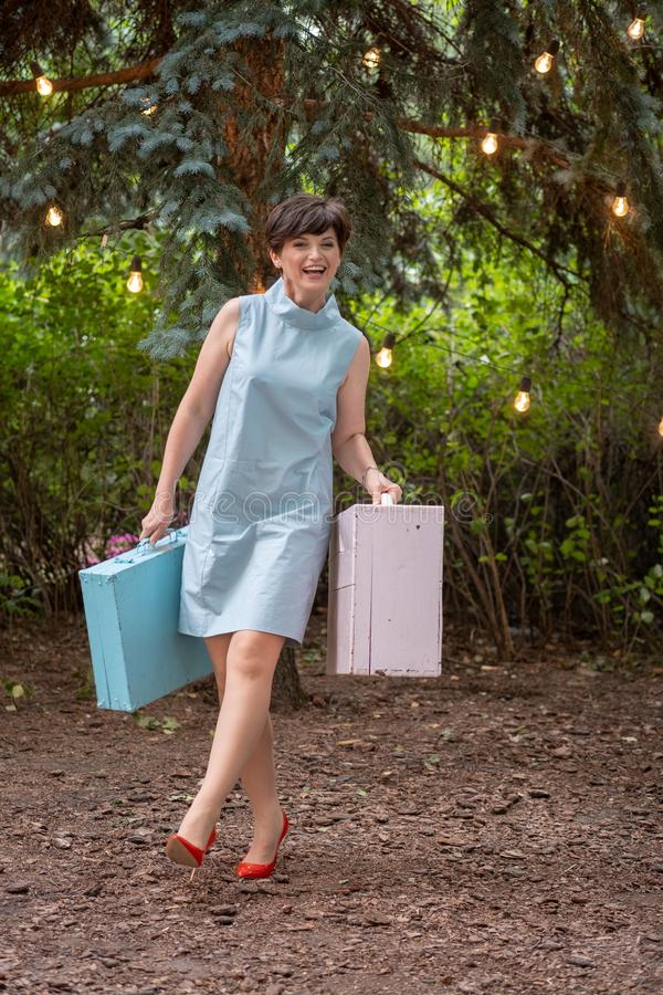 Happy woman smiling. Happy woman going on vacation. woman dressed in retro style. The woman smiles happily. Woman with suitcases outdoor. Happy woman going on royalty free stock photography
