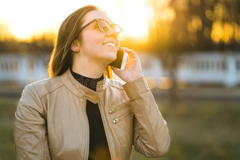 Happy woman smiling and laughing while talking on the phone royalty free stock image