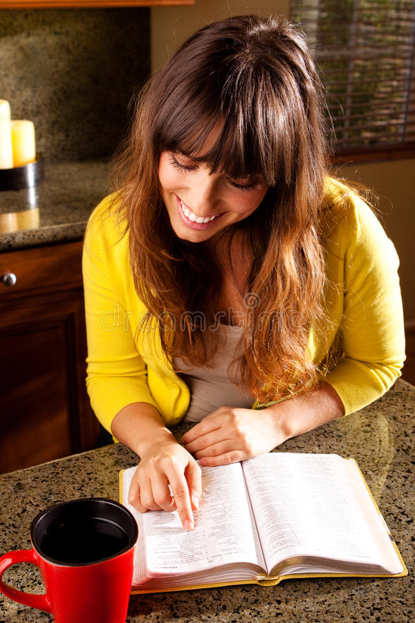 Happy woman smiling and reading the Bible. royalty free stock photos