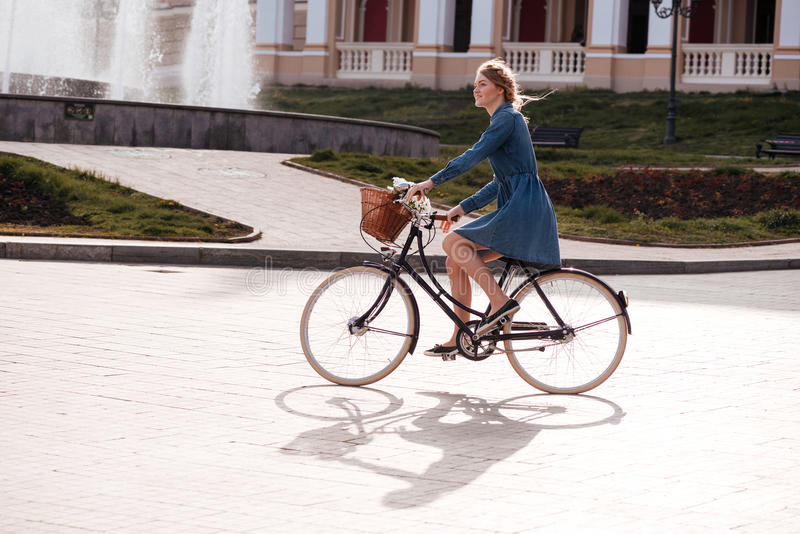 Happy woman smiling and riding a bike in the city stock photos