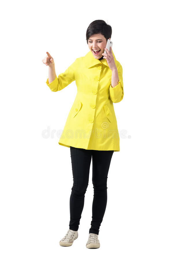 Happy woman smiling while talking on the cellphone looking down and pointing finger away stock images