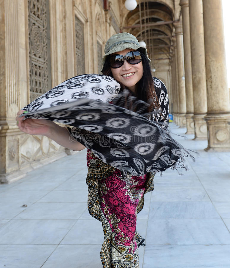 Happy woman. Smiling woman twirling colorful scarf standing in outdoor breezeway in daytime royalty free stock photos