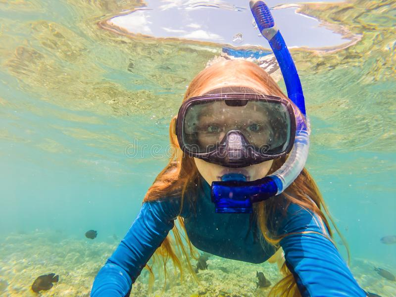 Happy woman in snorkeling mask dive underwater with tropical fishes in coral reef sea pool. Travel lifestyle, water. Sport outdoor adventure, swimming lessons royalty free stock photo