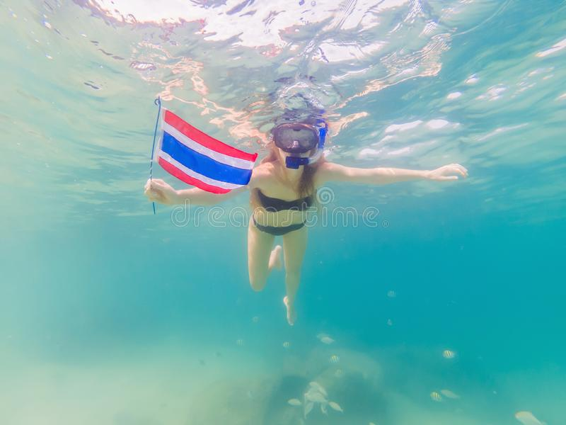 Happy woman in snorkeling mask dive underwater with tropical fishes with thailand flag in coral reef sea pool. Travel royalty free stock photos