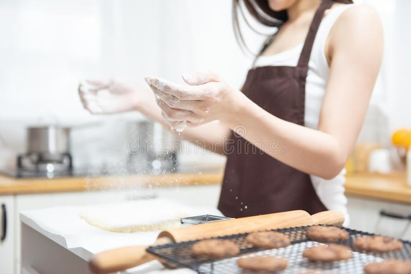 Woman sprinkling flour. Happy Woman sprinkling flour over dough on kitchen table. Baking bread stock photography