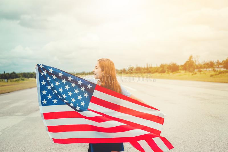 Happy woman standing with American flag Patriotic holiday.USA ce stock photo