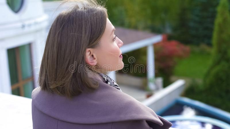 Happy woman standing on balcony of estate, breathing fresh air, secured life stock photos
