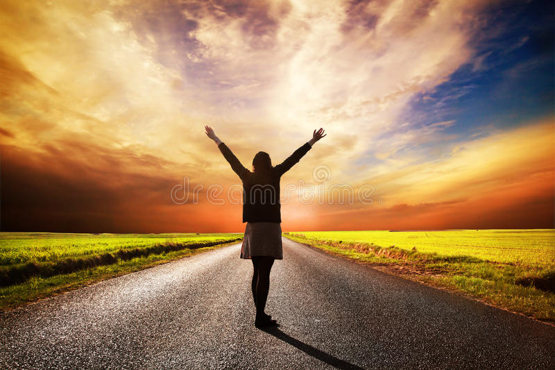 Happy woman standing on long road at sunset royalty free stock photos
