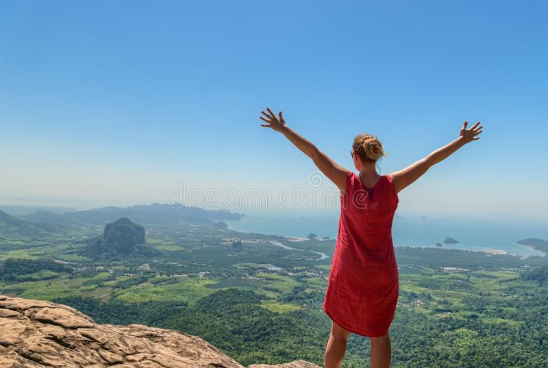Happy woman standing on mountain top royalty free stock image