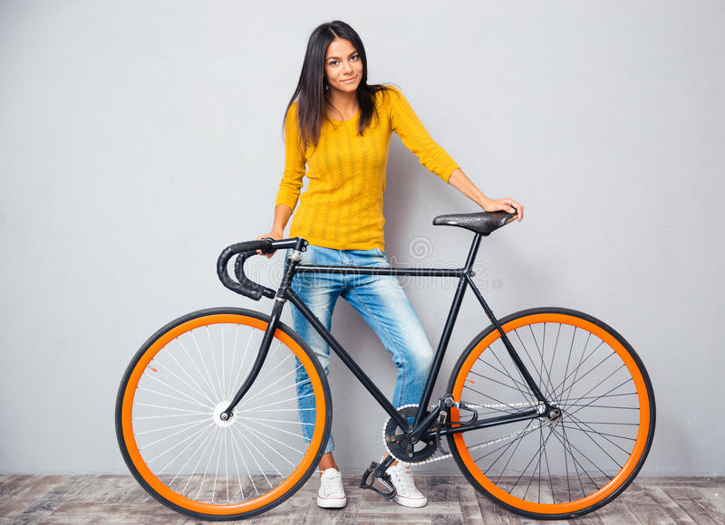 Happy woman standing near bicycle. Full length portrait of a happy woman standing near bicycle on gray background. Looking at camera royalty free stock images