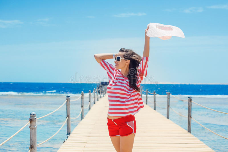 Happy woman standing on pier with big white hat.  stock photography