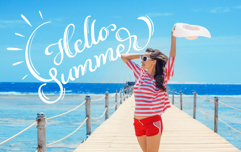 Happy woman standing on pier with big white hat and text Hello Summer. Calligraphy lettering stock photos