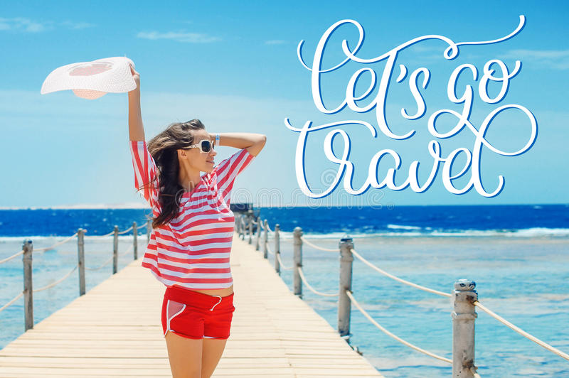 Happy woman standing on pier with big white hat and text Lets go travel. Calligraphy lettering hand draw stock image
