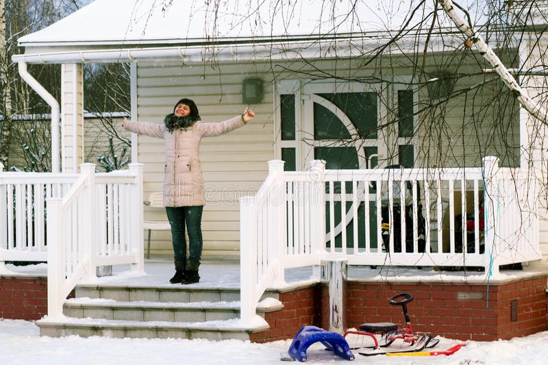 Happy woman standing raising hands on the porch of a country house in snowy winter day stock image