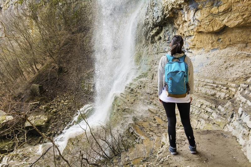 Hiker Woman Looking a Big Waterfall in the Rocks. Happy woman standing on a rocks and enjoying the stunning view in the spring mountain with lush waterfall royalty free stock image