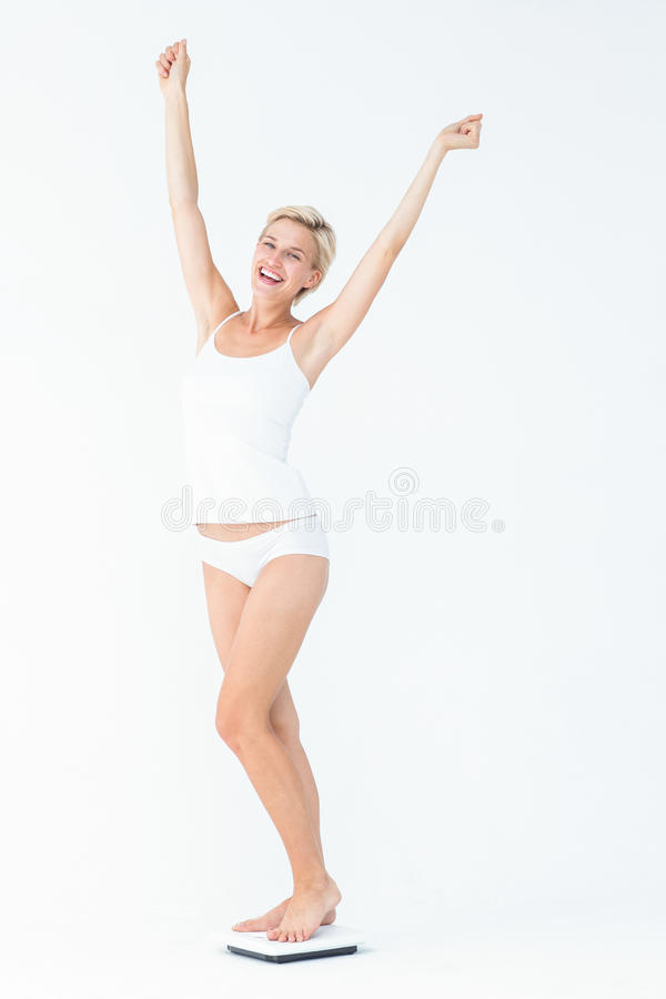 Happy woman standing on a scales spreading her arms royalty free stock photography