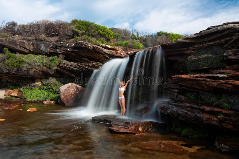 Happy woman standing under a waterfall in bushland wilderness royalty free stock photo