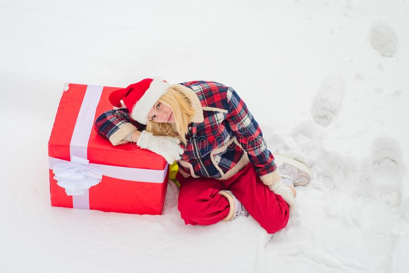 Happy woman standing on white snow background and holding a giant red gift box with both hands. Christmas Girl holding a stock photos
