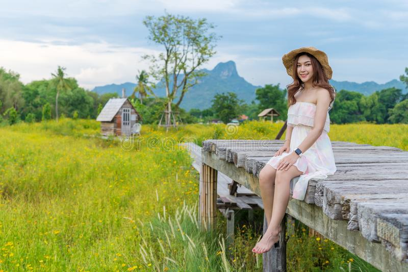 Woman sitting on wooden bridge with yellow cosmos flower field royalty free stock images