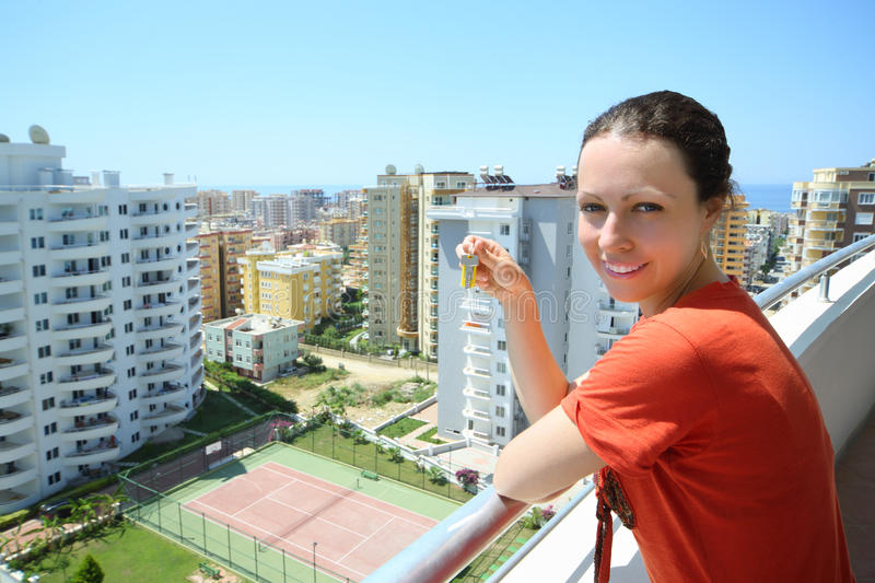 Happy woman stands on balcony royalty free stock photography