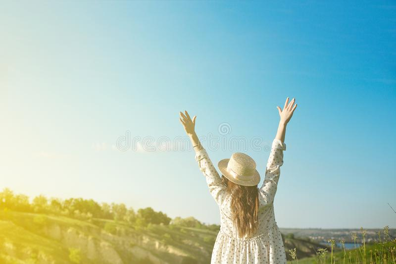 A happy woman in a straw hat with open arms stays on top of the edge of a mountain cliff under the sunset light of the royalty free stock photos
