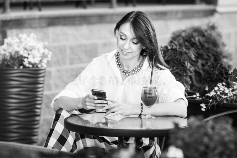 Happy woman in a street cafe reading a text message from her phone. Female making on-line shopping with internet on mobile phone royalty free stock image