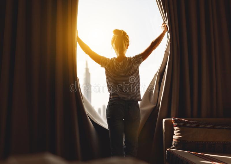 Happy woman stretches and opens curtains at window in morning. Happy woman stretches and opens the curtains at window in morning stock image